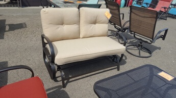 Outdoor Chocolate Metal Gliding Loveseat with Rounded Arms & Beige Cushions